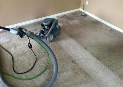 A carpet cleaning machine being used on a dirty carpet.